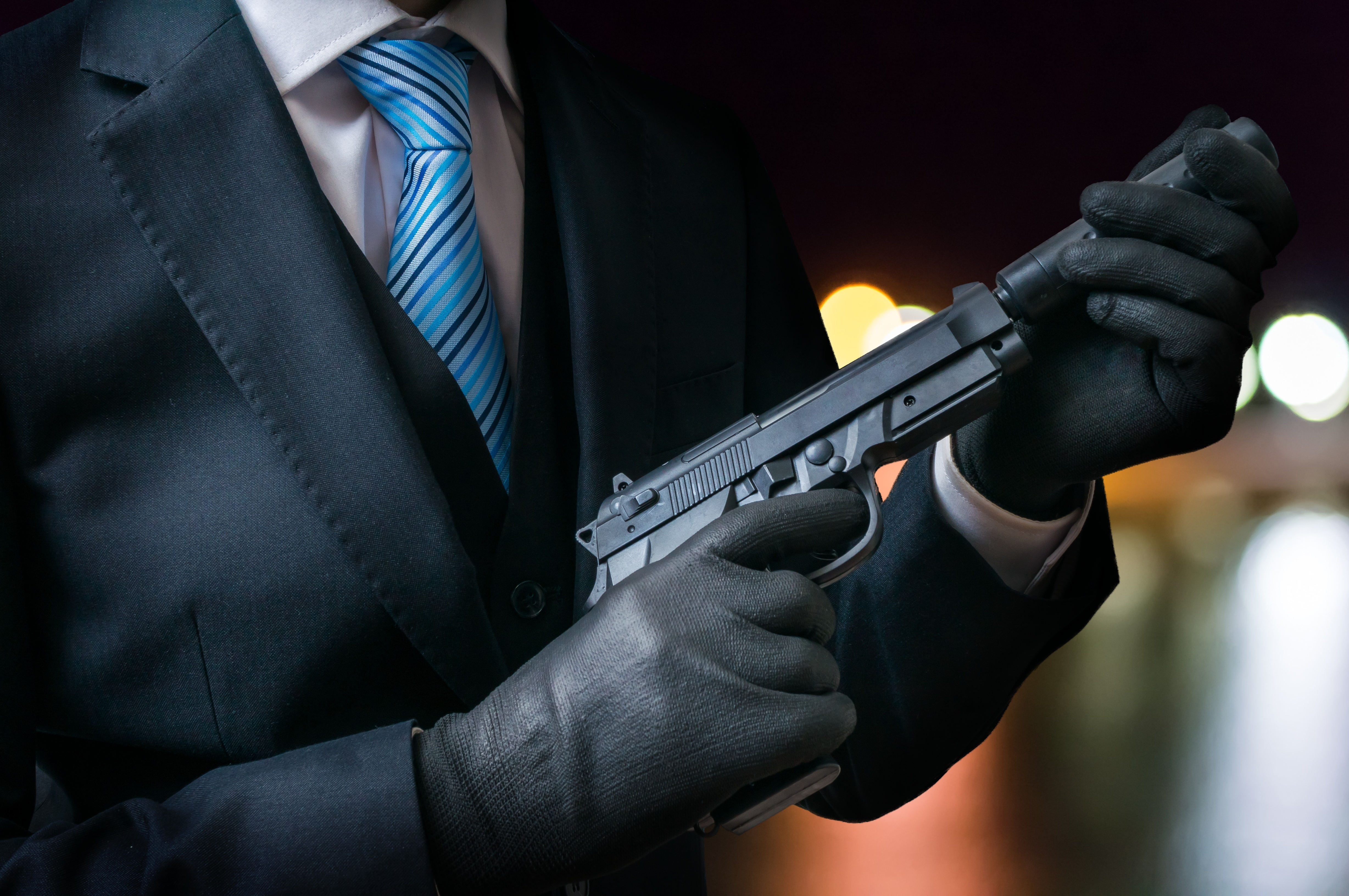 Killer holds gun with silencer in hands at night.