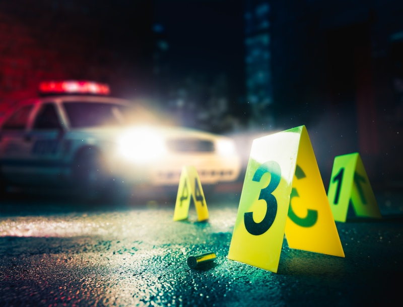 police car at a crime scene with evidence markers, high contrast image