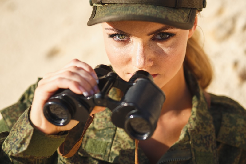 Gorgeous young woman in a Military costume with a binoculars on the background of a dessert
