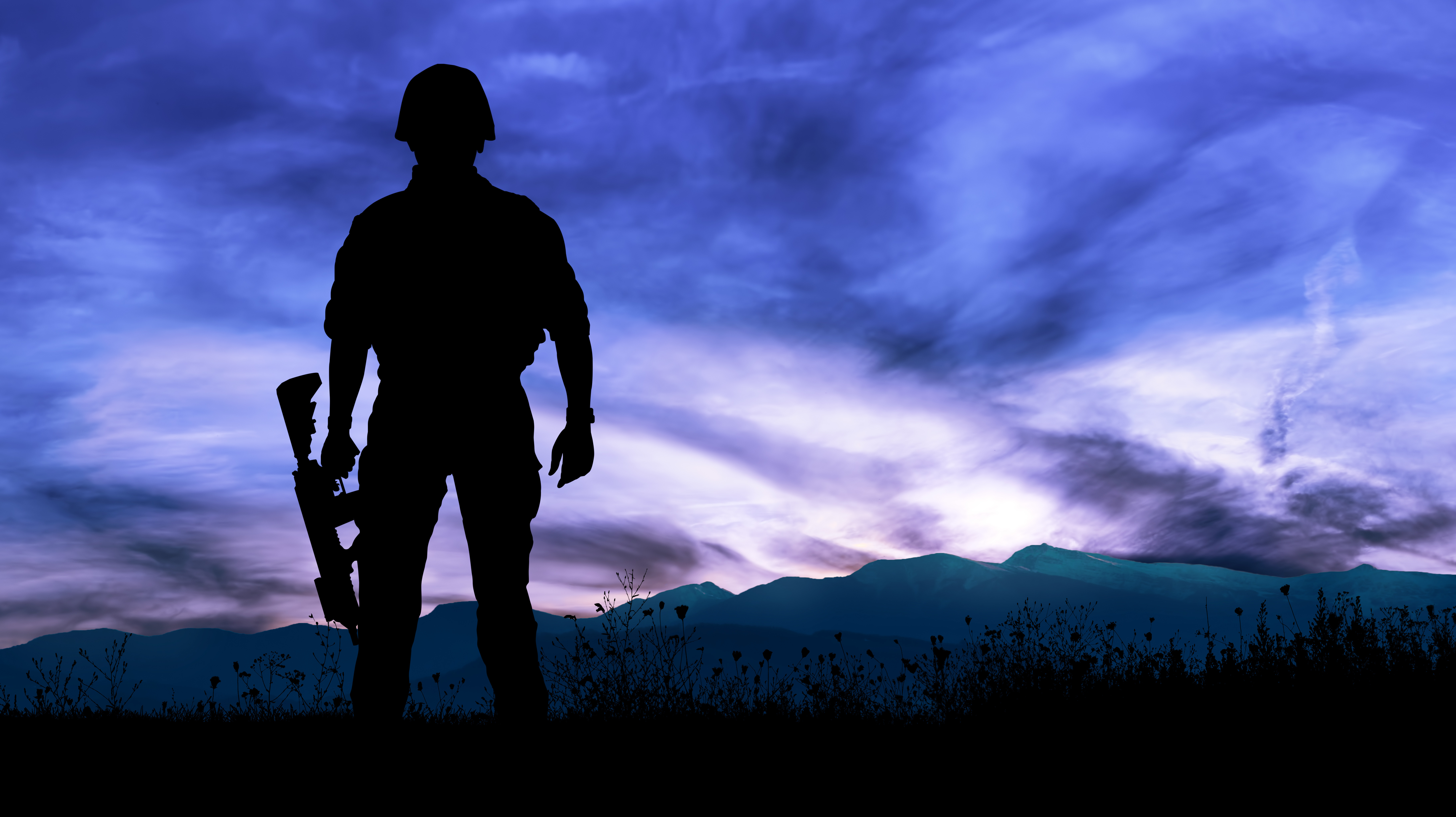Silhouette of military soldier or officer with weapons at night