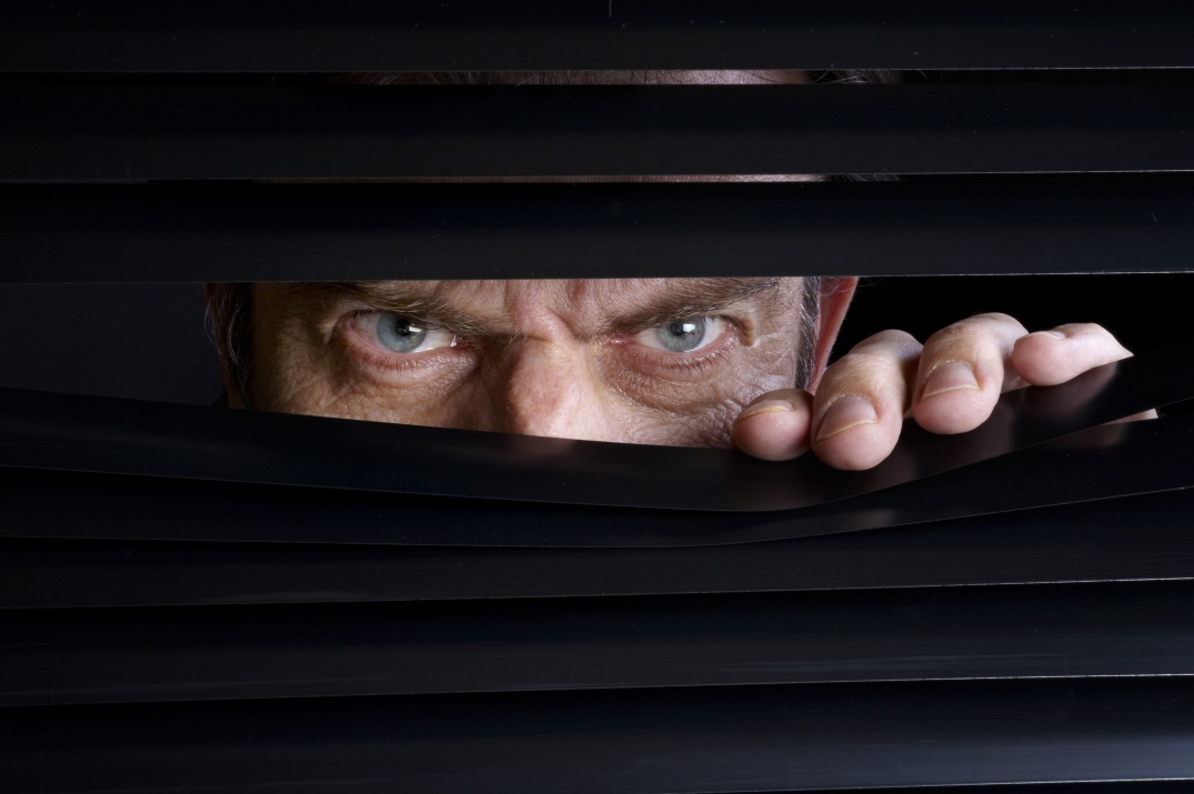 Man spying on something through venetian blinds