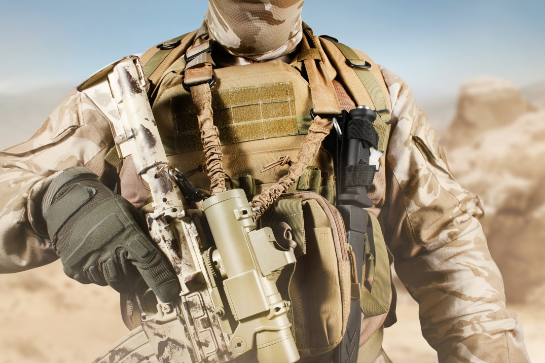 Soldier in uniform standing with rifle in desert.
